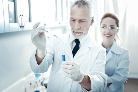 Selective focus of a test tube being held by a nice smart professional scientist while taking a biological test sample Stock Photo