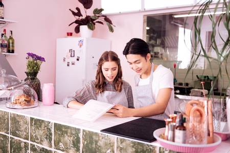 Dark-haired owner wearing white shirt giving important tasks his young waitress