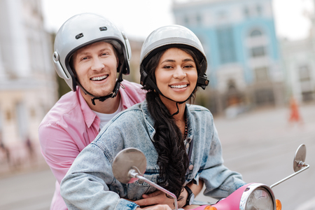 Merry optimistic couple wearing helmets and looking at camera