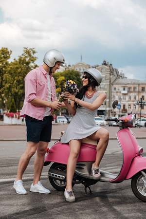 Vigorous happy woman sitting on motorbike and man giving flowers