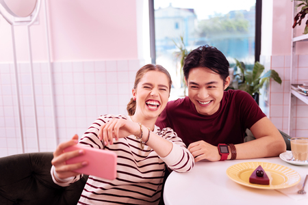 Laughing beautiful girlfriend feeling amazing while making memorable selfie with her man
