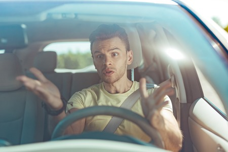 Angry emotional man driving his car without knowing the road to the seaside