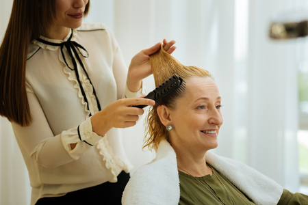 Portrait of a positive blonde woman smiling while waiting for a new hairstyle Stok Fotoğraf