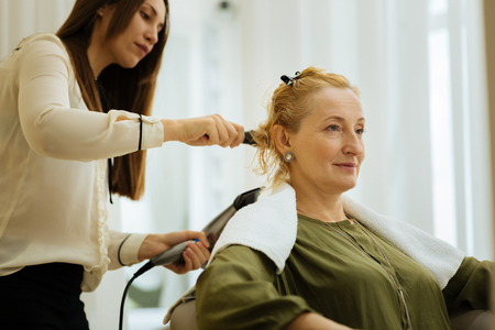 Nice cheerful woman smiling while waiting for a new hairstyle to be done