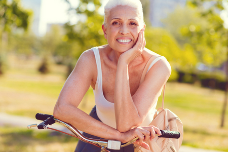 Waist up shot of an elderly lady of heavenly beauty resting her chin on a hand while standing in a park and smiling after bicycling outdoors. Stock Photo