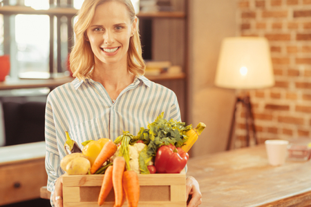 Love cooking. Portrait of smiling female that looking at camera and feeling happiness while holding box with organic vegetables Reklamní fotografie