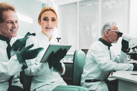 Green-eyed bioengineer. Green-eyed experienced bioengineer sitting near her professional colleagues while cooperating with them