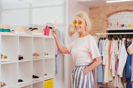 Modern retired woman wearing yellow sunglasses making selfie while shopping in the mall