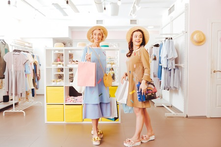 Stylish beaming mother leaving showroom with purchases along with daughter 写真素材