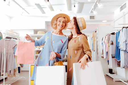 Fashionable loving daughter thanking her mother for wonderful shopping time