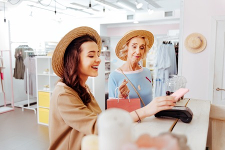 Modern daughter paying for her purchases while shopping with her appealing mother