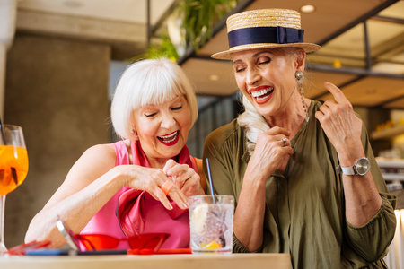 Positive age woman showing the ring while being with her sister in the cafe
