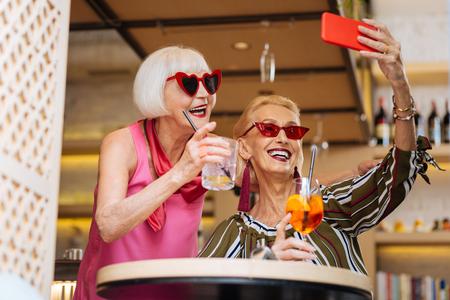 Happy cheerful women wearing sunglasses while taking selfies 免版税图像
