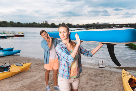 Blue boat. Young beautiful couple holding blue boat while preparing for adventurous river ride 版權商用圖片
