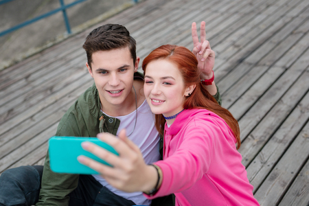 Sweet memories. Joyful young couple sitting together while taking a selfie Reklamní fotografie