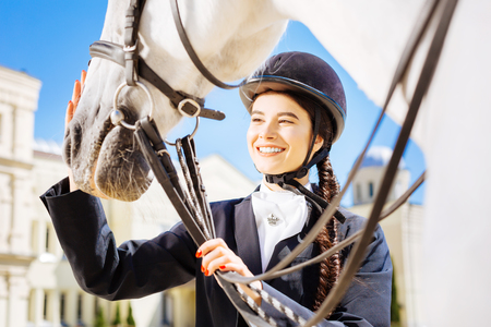 Beaming dark-haired horsewoman with long fishtail petting her white horse
