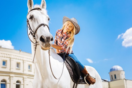 Beaming stylish schoolgirl touching her white racing horse while sitting on him