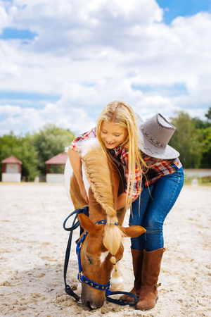 Kind-hearted pleasant good-looking schoolgirl playing with little cute pony with braid