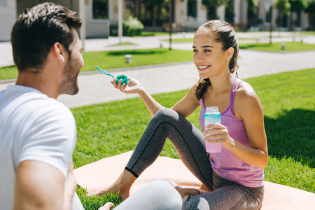 Delighted positive woman holding a bottle of water while talking to her boyfriend