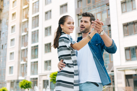 Joyful delighted couple dancing while enjoying their rime together Stock Photo