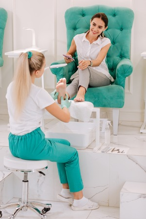 Pedicure master. Professional blonde-haired pedicure master feeling busy while working hard in beauty salon