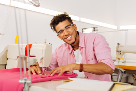 Feeling excited. Positive young tailor smiling happily and enjoying his working day in the modern atelier while sitting next to the sewing machine