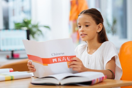 Exciting moment. Attentive serious kid reading a story in a book while sitting in a room
