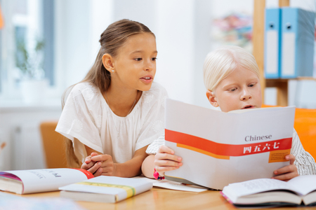 New language. Smart children being concentrated while learning Chinese together Stock Photo