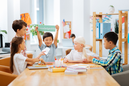 Games. High-spirited kids playing a game while being in a classroom Stock Photo