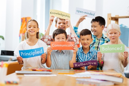 Studying time. Smiling joyful schooldchildren standing in the middle of a classroom while holding tables in their hands Banco de Imagens