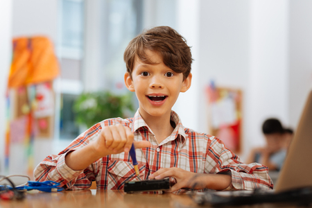 Wow. High-spirited smiling boy looking at you while dealing with a new device Imagens