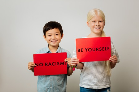 No racism. Smart children holding tables against racism while standing in a room 스톡 콘텐츠