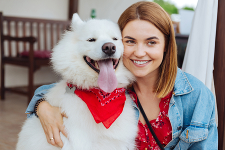 White fluffy husky wearing red bandanna on his neck coming to beautiful beaming owner