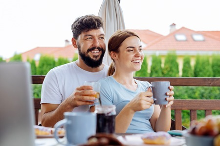 Juice and coffee. Happy couple feeling relaxed and relieved while drinking orange juice and coffee in the morning