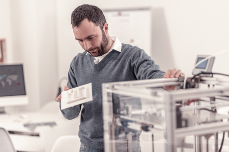 Thoughtful smart man making model on 3D printer working on project Stock Photo