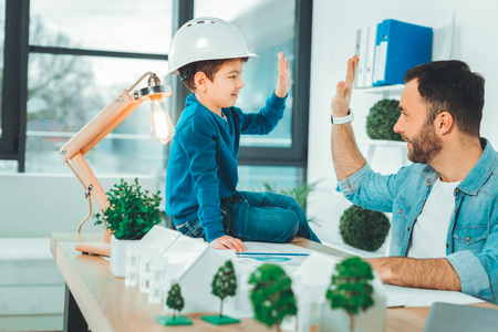 Friendly atmosphere. Kind boy wearing helmet while touching hands with father Stock Photo