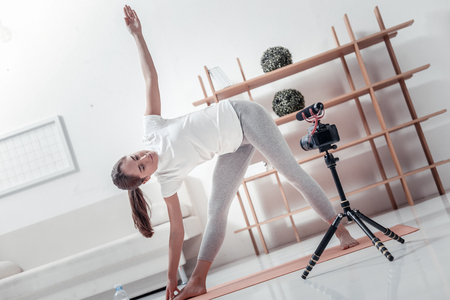 Morning exercises. Sporty beautiful woman doing slopes standing in front of camera at home Stock Photo