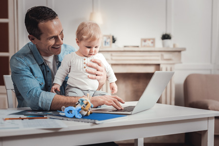 Digital device. Positive joyful man sitting at the laptop while holding his child
