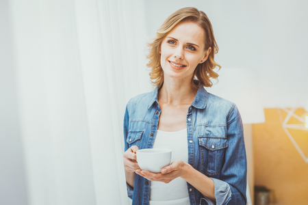 Dreamy mood. Charming blonde female keeping smile on her face while being deep in thoughts Stock Photo