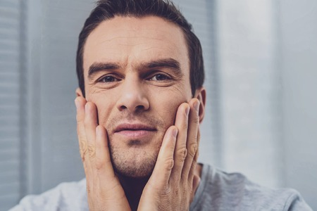 Handsome hazel-eyed man feeling very surprised after hearing unexpected news from his colleague