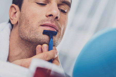 Man with razor. Dark-eyed pleasant man scraping his chin while holding little blue razor in his hand Imagens