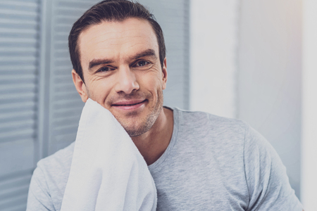 Handsome man. Handsome pleasant man feeling relieved while toweling off his chin after shaving in the bathroom