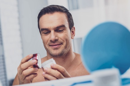 Face cream. Hazel-eyed pleasant looking man opening moisturizing face cream while getting ready for work in the morning