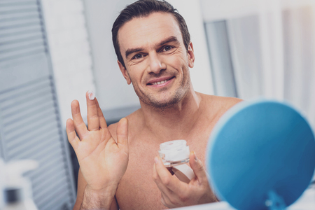 Smiling muscleman. Smiling beaming muscleman using face cream while standing near toilet table