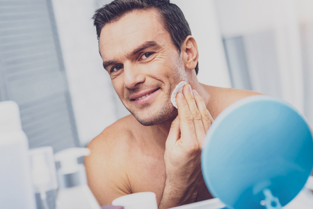 Beaming man. Beaming muscleman caring about his skin holding cotton wool in hand while standing in front of mirror