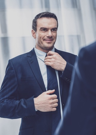 Fashion. Personable delighted entrepreneur being in a good mood and selecting a tie for todays business suit while looking in a large mirror with a smile