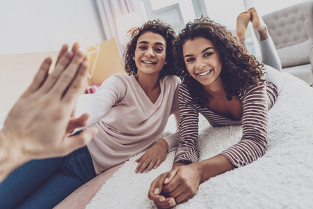 Strong friendship. Attractive brunettes lying on the bed while giving high five