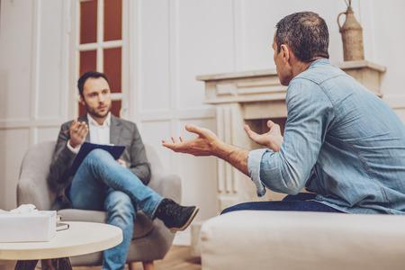 Paciente serio sentado en semi posición y gesticulando activamente mientras resuelve problemas con el psicólogo