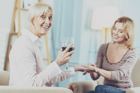 Cheerful aged woman drinking a glass of wine while celebrating the engagement of her daughter