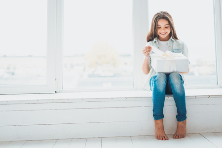 Unexpected surprise. Curious smiling girl feeling amused while opening her unexpected wonderful surprise from parents
